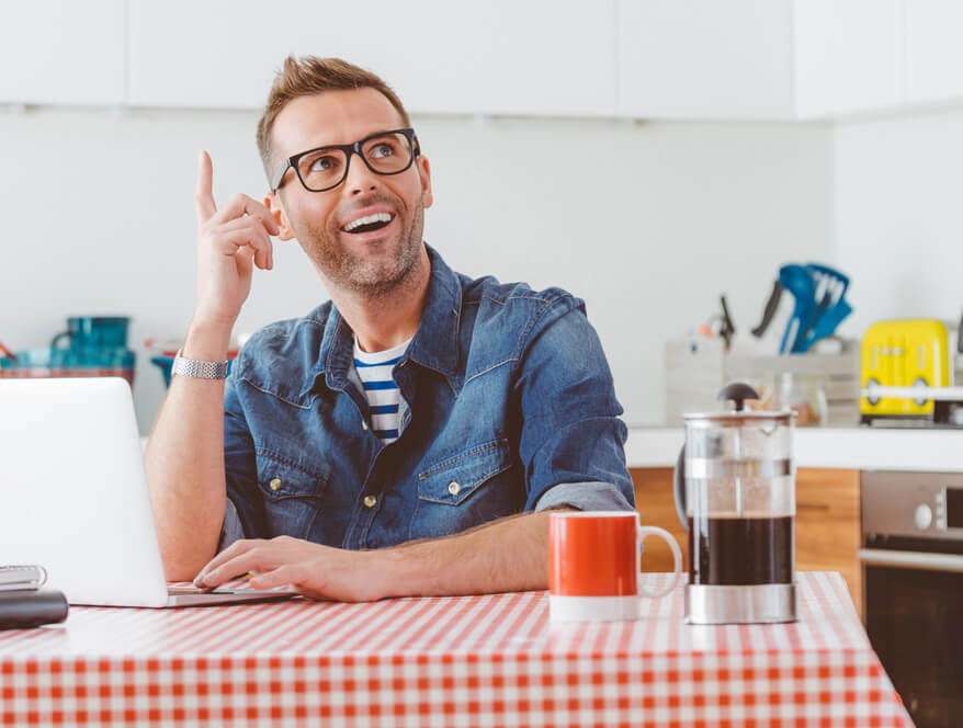 He is not leaving money on the table.. Happy man wearing jeans shirt and glasses sitting at the kitchen table at home, working on laptop, looking up and laughing.