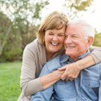 retired couple smiling at a park